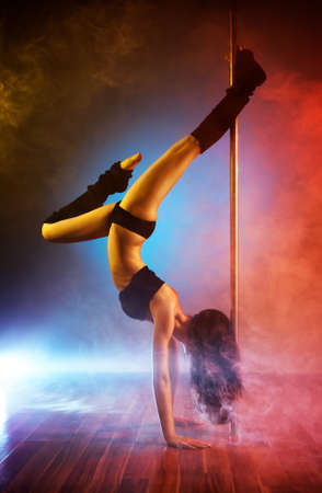 pole dance: Young pole dance woman with smoke effect. Stock Photo
