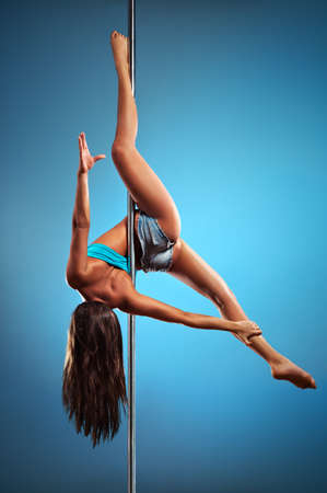 Young pole dance woman on blue background. Stock Photo - 11863930