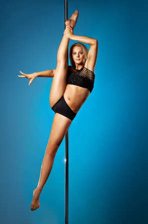 Young pole dance woman on blue background. photo