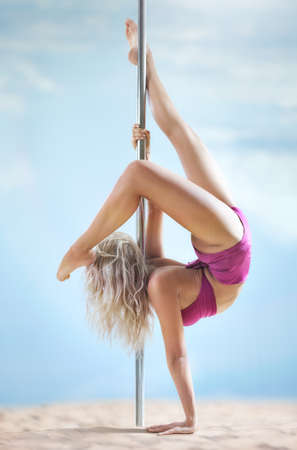 poledance: Young slim pole dance woman on summer beach. Stock Photo