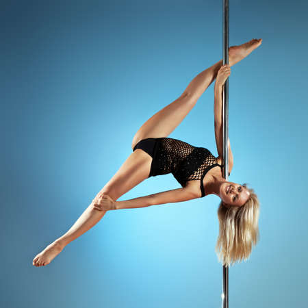 nude gymnast: Young pole dance woman on blue background.