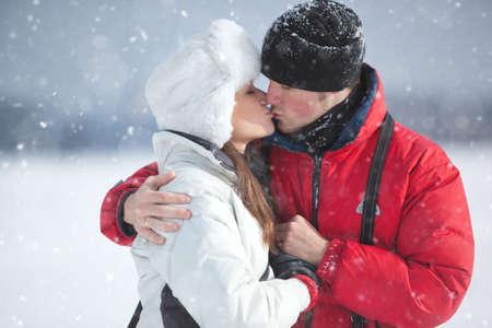 novios besandose: Pareja joven besando el invierno retrato al aire libre.