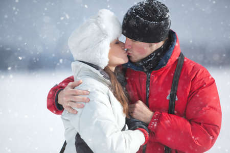 snow woman: Young couple kissing winter outdoors portrait. Stock Photo