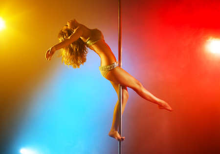 pole dance: Giovane danza donna pole con luci colorate. Archivio Fotografico