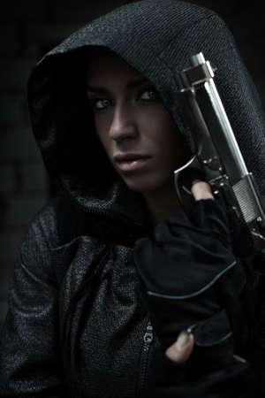 mujer con pistola: Peligro mujer con arma de fuego. Los colores oscuros.