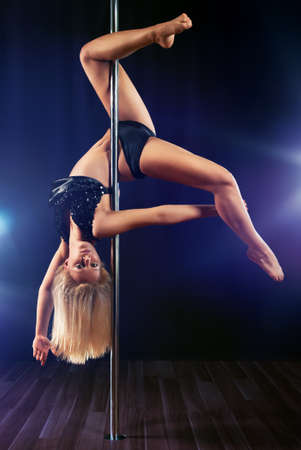 Young pole dance woman on dark background.