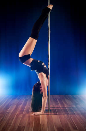 poledance: Young pole dance woman upside down. Stock Photo