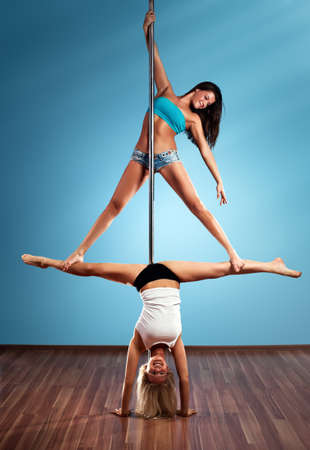 poledance: Two young pole dance women. Stock Photo