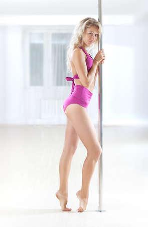 pole dance: Giovane donna pole dance in piedi al polo.