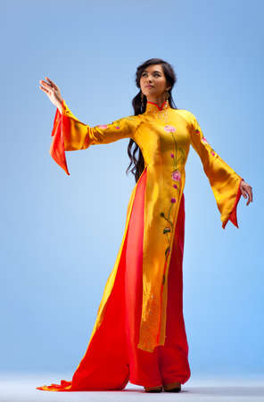 traditional clothes: Young vietnamese woman. On blue background. Stock Photo