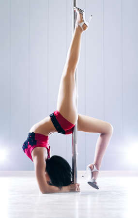 poledance: Young slim pole dance woman. Bright white colors.