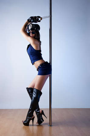 Young slim pole dance woman in police style. photo