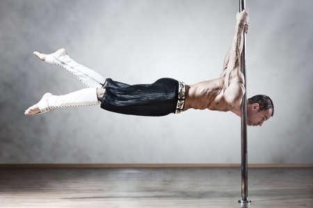 pole dancing: Jeune homme fort de pole dance.
