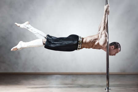 dancing pose: Young strong pole dance man.