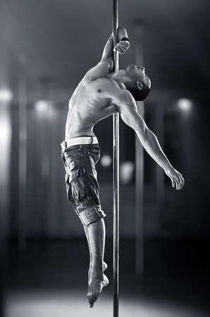 pole dancing: Jeune homme fort de pole dance
