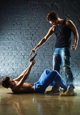 man holding gun: Men with guns fighting  Contrast colors