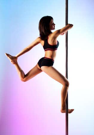 pole dance: Giovane donna danza pole su sfondo blu e rosa