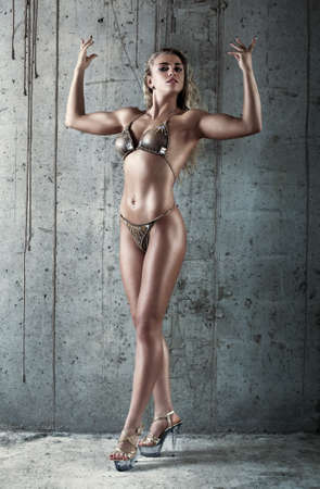 Young sexy muscular woman on wall background. photo