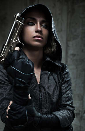 women with guns: Danger woman with gun. Dark colors. Stock Photo