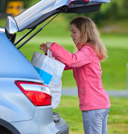 putting in: Young woman putting bag in car after shopping.