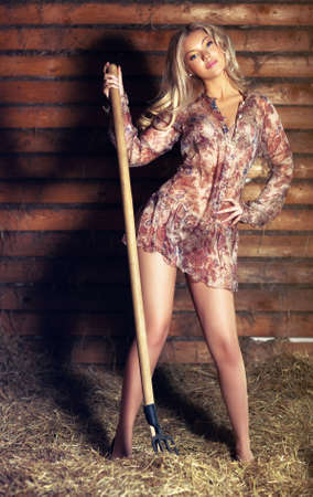 Young sexy woman with hay and a pitchfork  photo