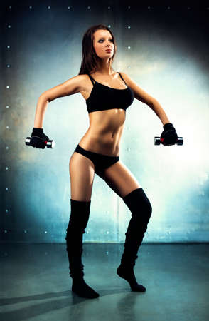 Young sexy fitness woman  On wall background  photo