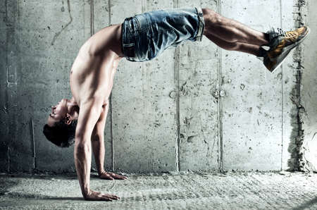break dancer: Young man sports exercises  On wall background
