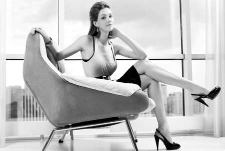 Young woman sitting on chair. Black and white. Stock Photo - 14011517