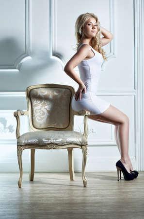 persona sentada: Joven mujer sentada en una silla en el fondo blanco de la pared