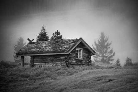 log on: Old traditional Norway house at foggy morning