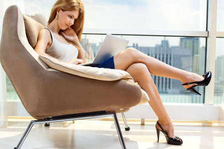 sexy business woman: Young woman sitting on chair with laptop  Stock Photo
