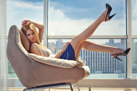 Young woman sitting on chair on window background