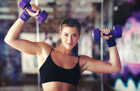 Young strong woman with dumbbells Stock Photo - 15036454