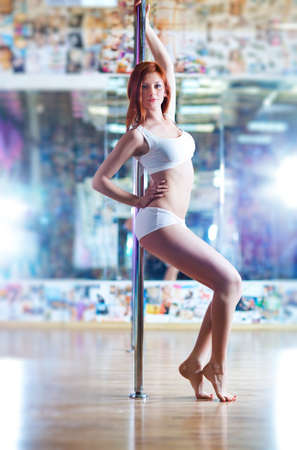 Young slim pole dance woman in sport club interior  photo