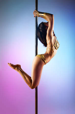 Young pole dance woman on blue and pink background  Stock Photo - 15036487