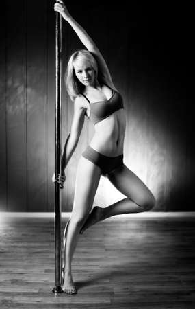 Young slim pole dance woman. Black and white. photo