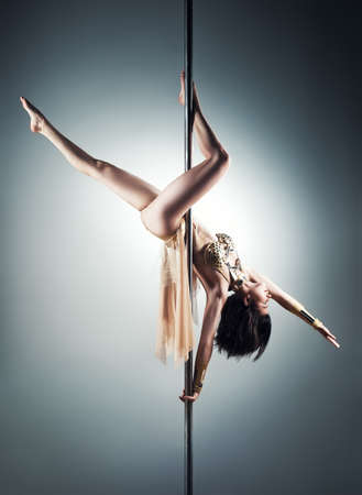 pole dance: Young slim pole dance woman.