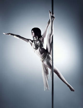 Young slim pole dance woman. Blue and white colors. photo