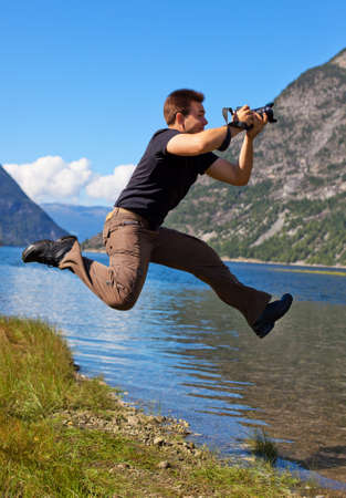 Young photographer shooting nature in the jump. photo