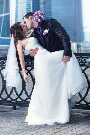 Young wedding couple kissing on city background. photo