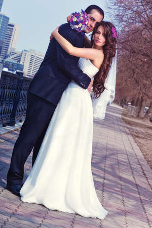 angle view: Young wedding couple on city background. Camera angle view.