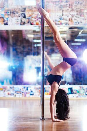 pole dancing: Jeune femme mince pole dance dans un club sportif d'int�rieur