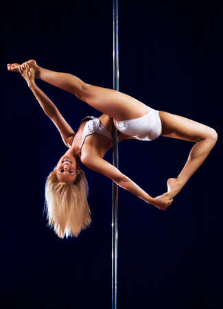 Young pole dance woman on dark background