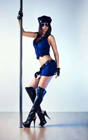 Young slim pole dance woman in police clothing  photo