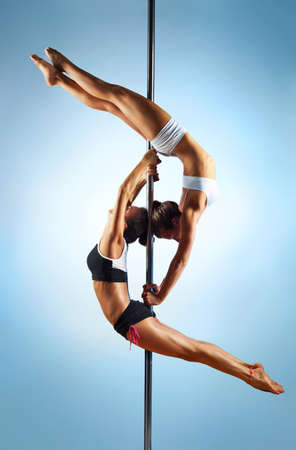 Two young slim pole dance women