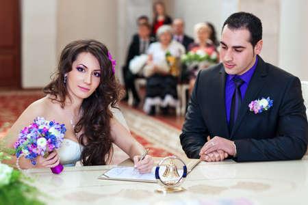 Young couple signing wedding documents  photo