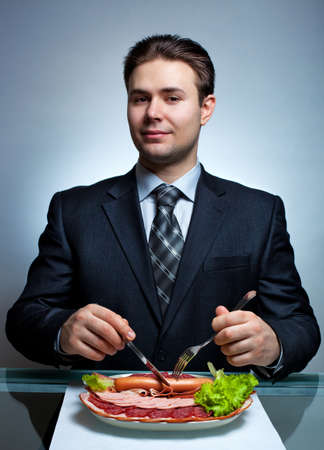 Young businessman eating  Rich meat menu  photo