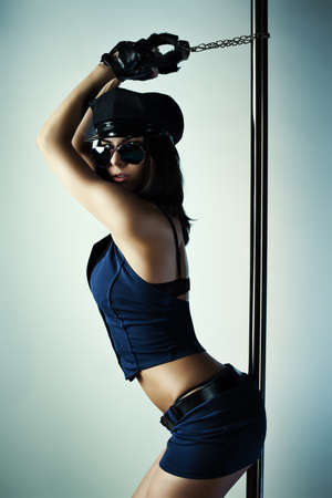 Young slim pole dance woman in police clothing. photo