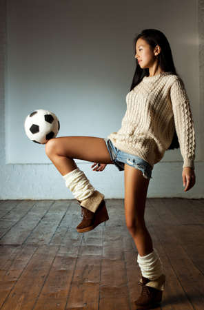Young slim japanese woman playing toy football. photo