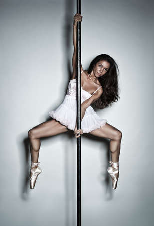 Young pole dance woman on wall background  photo